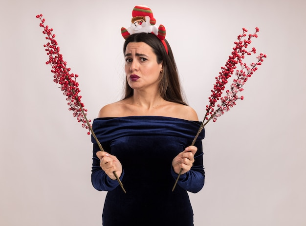 Unpleased young beautiful girl wearing blue dress and christmas hair hoop holding rowan branch isolated on white background