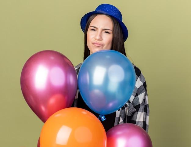 Una giovane bella ragazza scontenta che indossa un cappello blu in piedi dietro palloncini isolati su un muro verde oliva