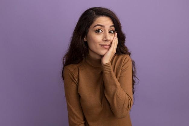 보라색 벽에 고립 된 뺨에 손을 넣어 갈색 터틀넥 스웨터를 입고 불쾌한 젊은 아름다운 소녀