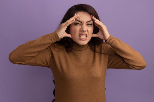 紫色の壁に隔離された寺院に手を置く茶色のタートルネックのセーターを着て不機嫌な若い美しい少女