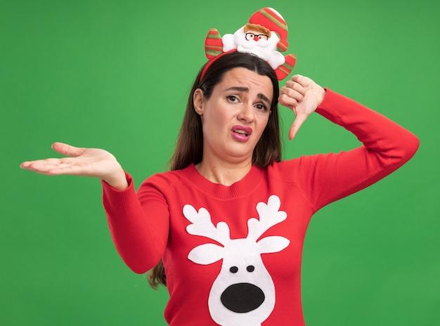 緑の壁に分離された側の手でポイントを親指を下に示すクリスマスの髪のフープとクリスマス セーターを着ている不愉快な美しい少女