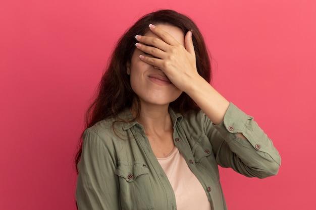 Недовольная молодая красивая девушка в оливково-зеленой футболке закрыла лицо рукой, изолированной на розовой стене