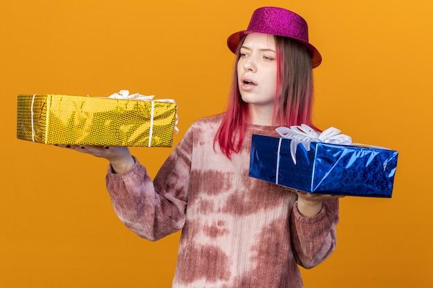 オレンジ色の壁に隔離されたギフトボックスを保持し、見てパーティーハットを身に着けている不機嫌な若い美しい少女 Premium写真