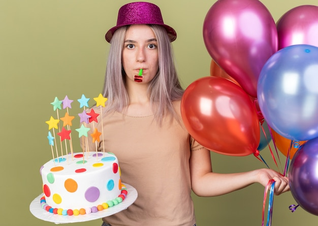 Unpleased young beautiful girl wearing party hat holding balloons with cake blowing party whistle isolated on olive green wall