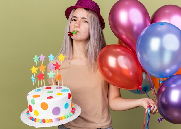 Unpleased young beautiful girl wearing party hat holding balloons with cake blowing party whistle