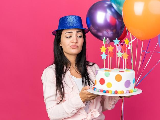 ピンクの壁に分離されたケーキと風船を保持しているパーティーハットを身に着けている不機嫌な若い美しい少女