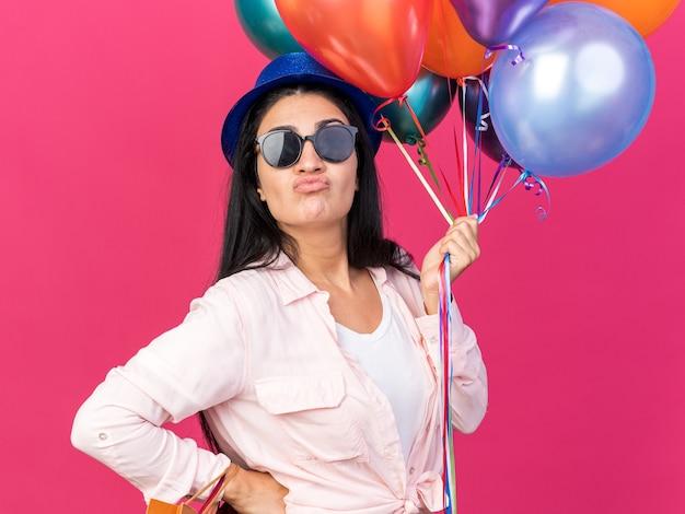 Una giovane bella ragazza scontenta che indossa un cappello da festa che tiene palloncini con sacchetti regalo che mettono la mano sull'anca isolata sulla parete rosa