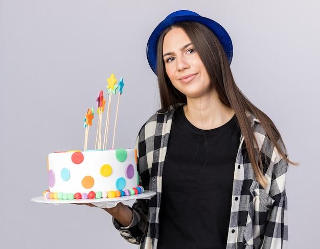 白い壁に隔離のケーキを保持しているパーティーハットを身に着けている不機嫌な若い美しい少女