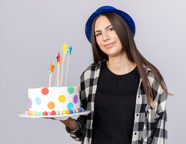 Unpleased young beautiful girl wearing party hat holding cake isolated on white wall