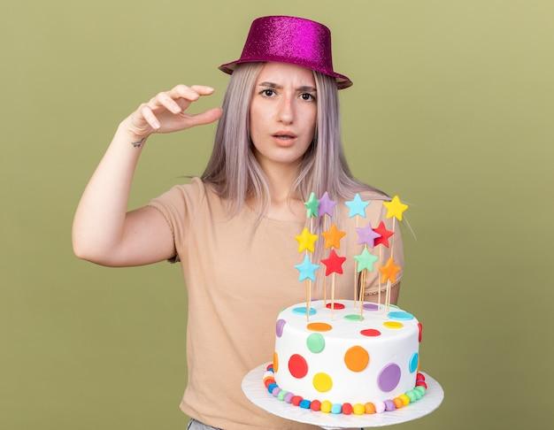 Una giovane bella ragazza scontenta che indossa un cappello da festa che tiene la torta alzando la mano isolata sul muro verde oliva