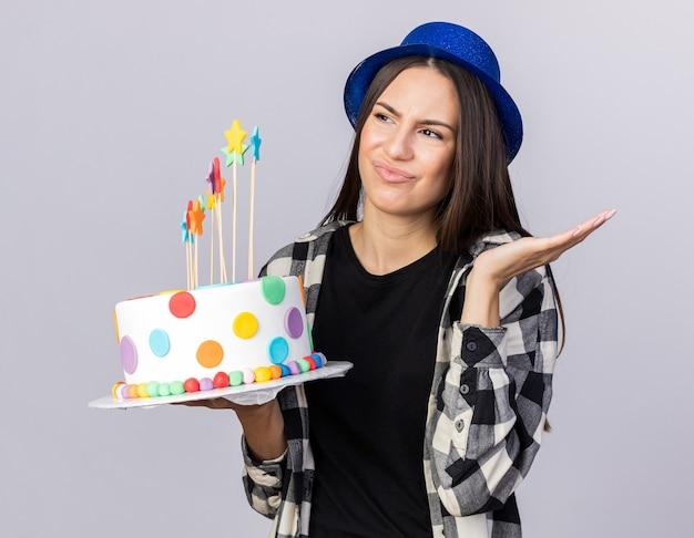 흰색 벽에 격리된 손으로 케이크를 펴고 파티 모자를 쓰고 있는 불쾌한 젊은 아름다운 소녀