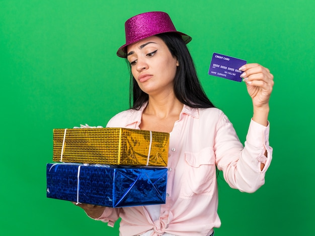 Unpleased young beautiful girl wearing party hat holding gift boxes with credit card