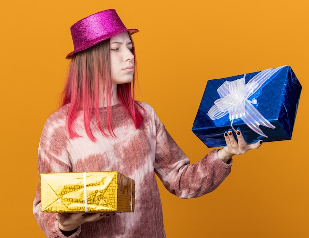 Unpleased young beautiful girl wearing party hat holding and looking at gift boxes isolated on orange wall