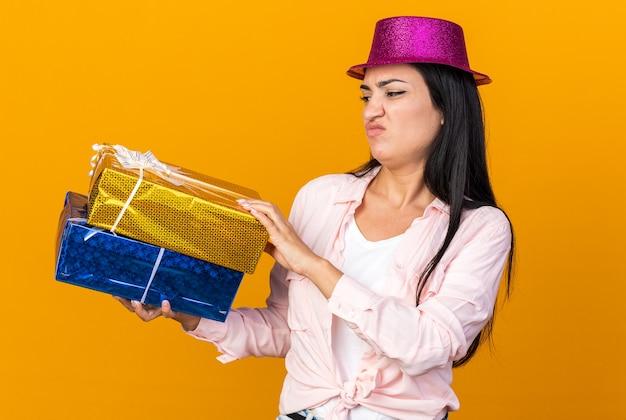Una giovane bella ragazza scontenta che indossa un cappello da festa che tiene in mano e guarda scatole regalo isolate sulla parete arancione