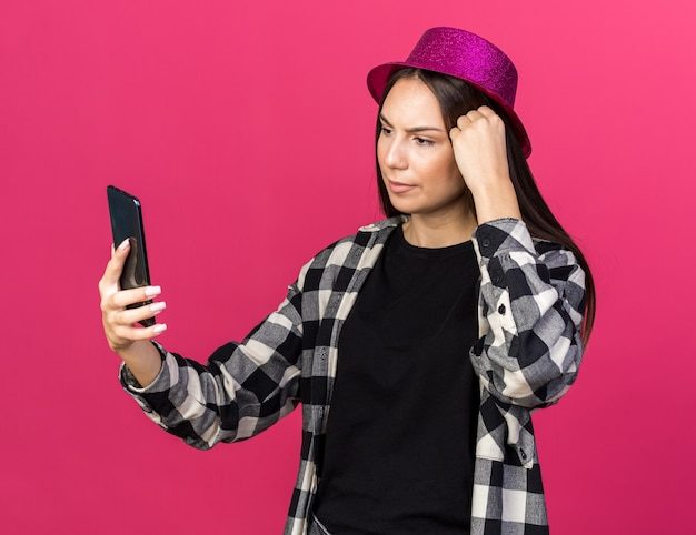Unpleased young beautiful girl wearing party hat holding and looking at phone