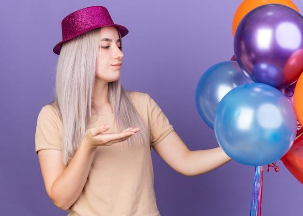 Una giovane bella ragazza scontenta che indossa un cappello da festa che tiene e indica con la mano i palloncini