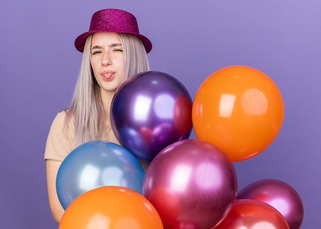 Unpleased young beautiful girl wearing party hat standing behind balloons showing tongue