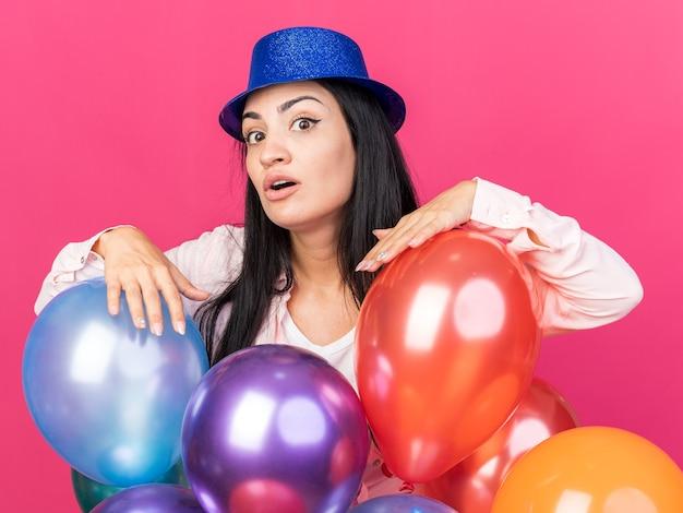 핑크색 벽에 격리된 풍선 뒤에 서 있는 파티 모자를 쓴 불쾌한 젊은 아름다운 소녀