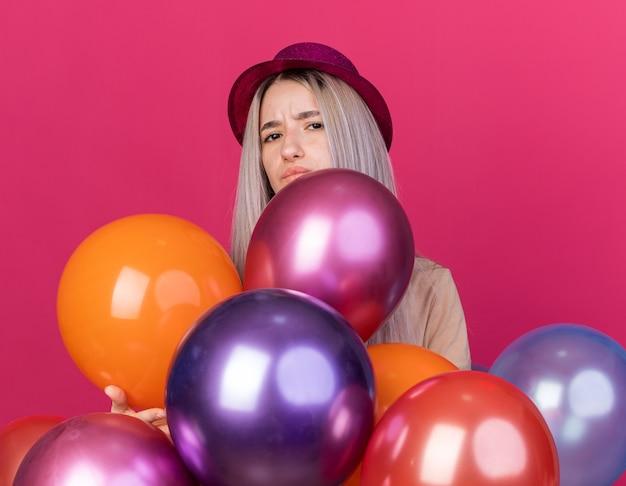 분홍색 벽에 격리된 풍선 뒤에 서 있는 치과 교정기가 달린 파티 모자를 쓴 불쾌한 젊은 아름다운 소녀