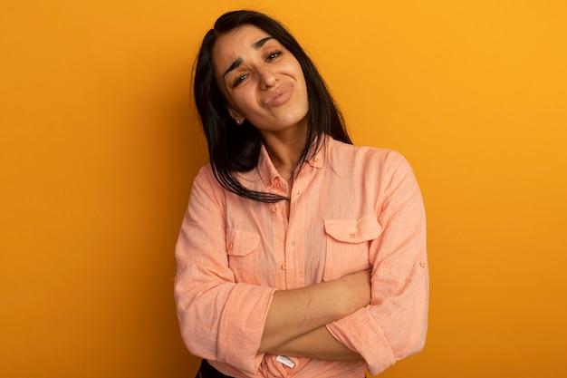 노란색 벽에 고립 된 분홍색 티셔츠 횡단 손을 입고 불쾌한 젊은 아름 다운 소녀