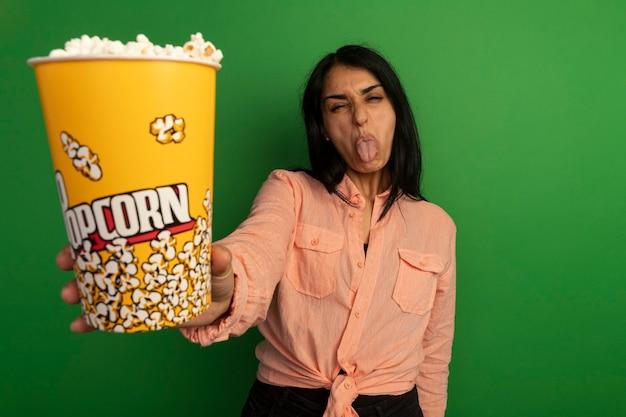 Недовольная молодая красивая девушка в розовой футболке держит ведро попкорна, показывая язык, изолированный на зеленом