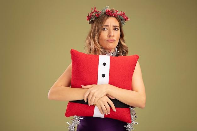紫色のドレスと花輪を首に花輪を身に着けている不機嫌な若い美しい少女は、オリーブグリーンの背景で隔離のクリスマス枕を抱きしめました