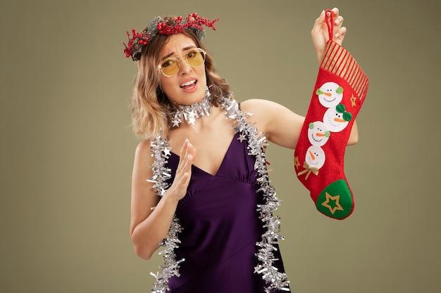 紫色のドレスと花輪を身に着けている不機嫌な若い美しい少女は、オリーブグリーンの背景で隔離のクリスマス靴下を保持している首にメガネと花輪