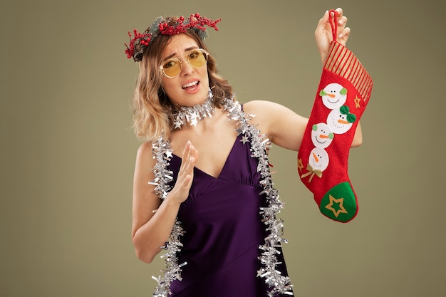 Unpleased young beautiful girl wearing purple dress and wreath with glasses and garland on neck holding christmas sock isolated on olive green background