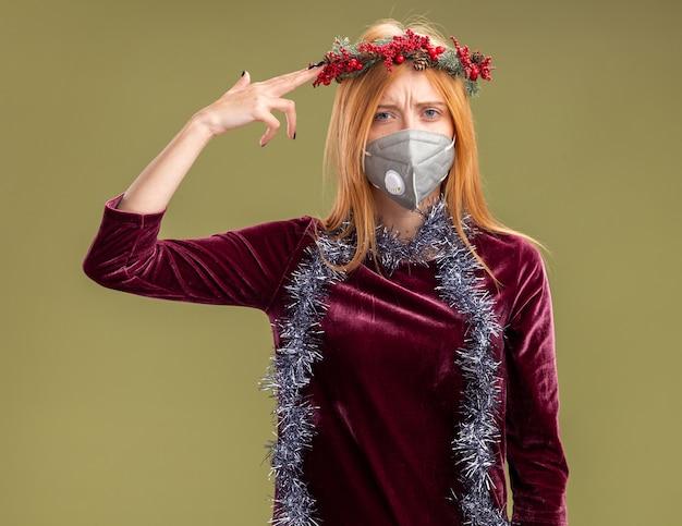Giovane bella ragazza insoddisfatta che indossa un vestito rosso con la corona e la mascherina medica con la ghirlanda sul collo che mostra il suicidio con il gesto della pistola isolato su fondo verde oliva