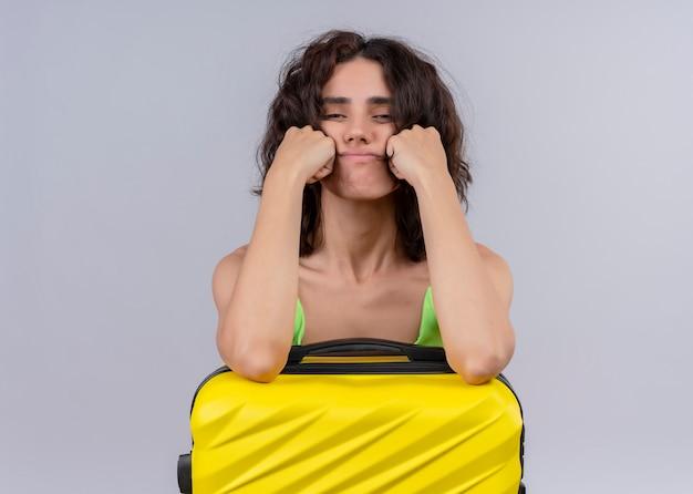 スーツケースに腕を入れて、孤立した白い背景の上の頬に手を入れて不快な若い美しい旅行者の女の子