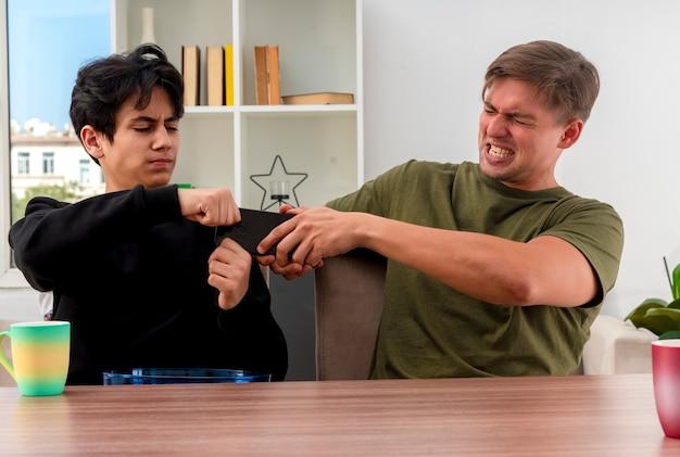 不機嫌な若いブロンドとブルネットのハンサムな男は、リビングルームの中で電話を持って引っ張ってテーブルに座っています