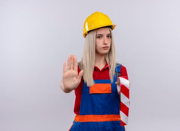コピースペースのある孤立した白い壁に手を身振りで示すスコッチテープを保持している制服を着た不機嫌な若いブロンドのエンジニアビルダーの女の子