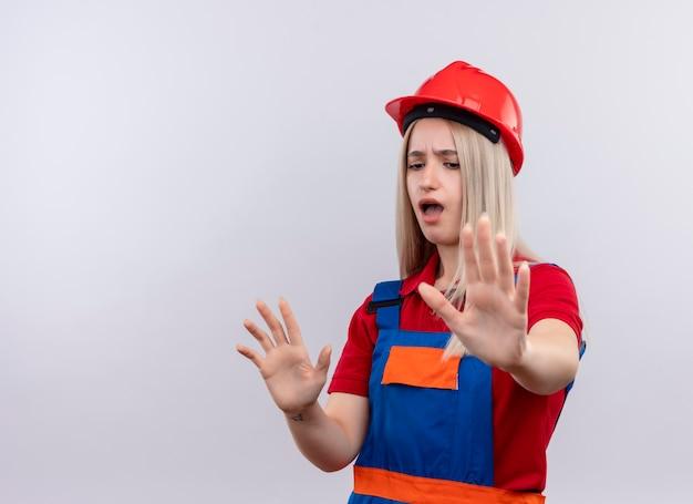 コピースペースのある孤立した白い壁に身振りで示す手を伸ばす制服を着た不機嫌な若いブロンドのエンジニアビルダーの女の子