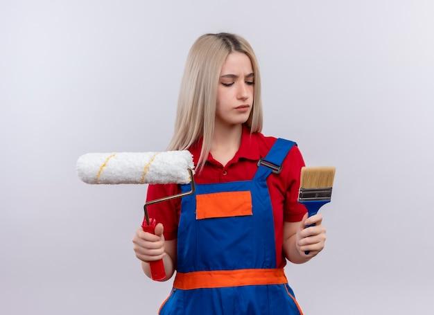 Ragazza bionda giovane costruttore ingegnere dispiaciuto in uniforme che tiene il pennello e il rullo di vernice guardandoli sulla parete bianca isolata
