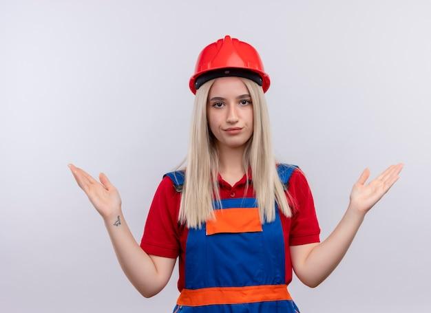Ragazza giovane bionda ingegnere costruttore dispiaciuto in uniforme che mostra le mani vuote sulla parete bianca isolata
