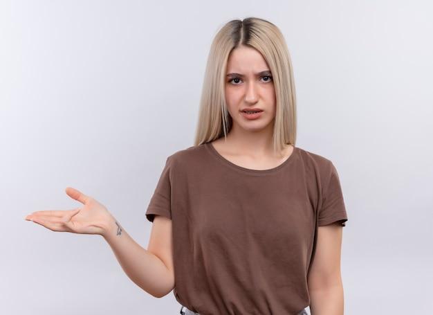 Giovane ragazza bionda dispiaciuta che mostra la mano vuota sulla parete bianca isolata