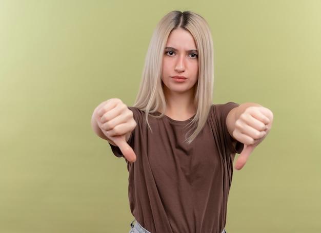 복사 공간이 격리 된 녹색 벽에 아래로 엄지 손가락을 보여주는 불쾌한 젊은 금발 소녀