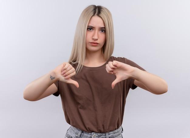 격리 된 흰 벽에 아래로 엄지 손가락을 보여주는 불쾌 하 게 젊은 금발 소녀