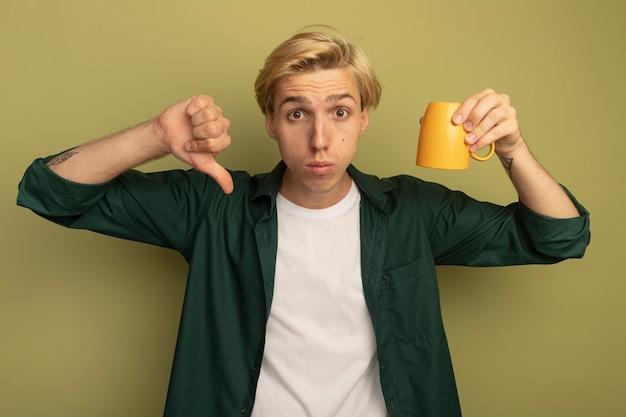 아래로 엄지 손가락을 보여주는 컵을 들고 녹색 티셔츠를 입고 불쾌한 젊은 금발의 남자