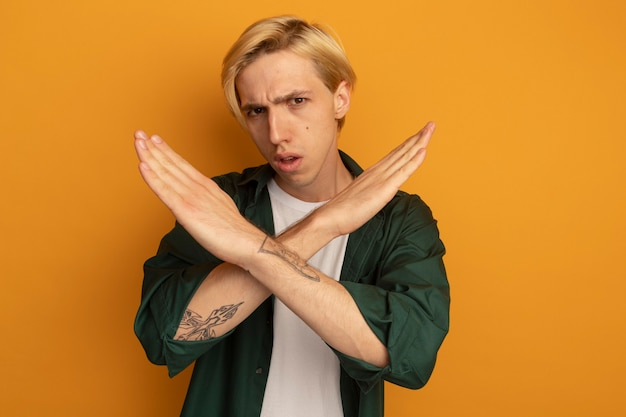 Недовольный молодой блондин в зеленой футболке, показывающий жест нет