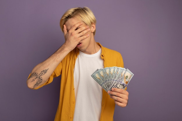 Unpleased young blonde guy wearing yellow t-shirt covered face with hand and holding cash isolated on purple