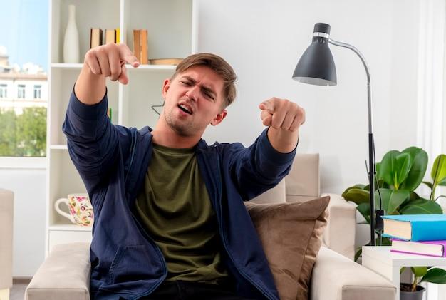 Il giovane uomo bello biondo dispiaciuto si siede sulla poltrona che indica alla macchina fotografica con due mani all'interno del soggiorno