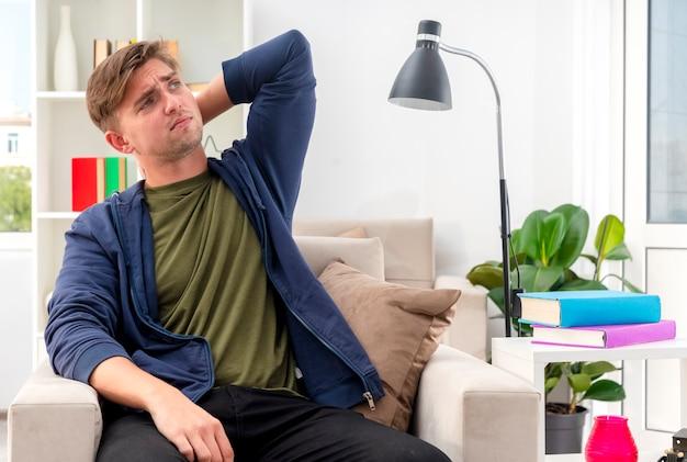 不機嫌そうな若いブロンドのハンサムな男は、リビングルームの後ろの首に手を置いて肘掛け椅子に座っています