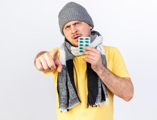 겨울 모자와 스카프를 착용하는 불쾌한 젊은 금발의 아픈 남자는 흰 벽에 고립 된 앞에서 가리키는 의료 약 팩을 보유하고 있습니다.