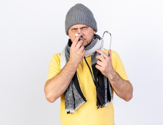 겨울 모자와 스카프를 착용하는 불쾌한 젊은 금발의 아픈 남자는 흰 벽에 고립 된 청진기를 보유하고 있습니다.