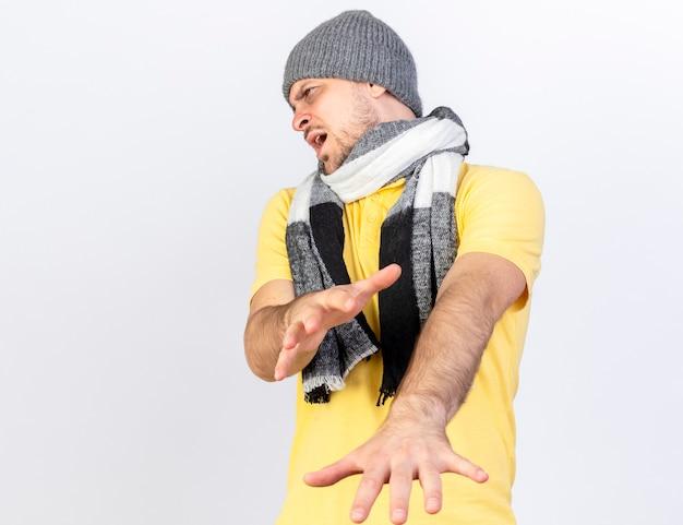 冬の帽子と白い壁に隔離された手を伸ばしてスカーフを身に着けている不機嫌な若い金髪の病気の男