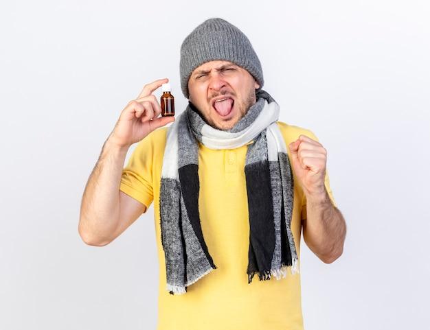 Il giovane uomo malato biondo dispiaciuto che indossa il cappello e la sciarpa di inverno tiene la medicina in bottiglia di vetro e tiene il pugno isolato sulla parete bianca