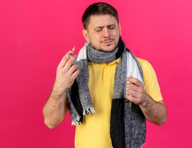 Недовольный молодой блондин больной славянский мужчина в шарфе держит шприц и ампулу на розовом