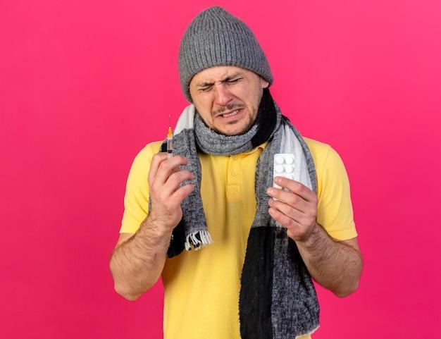 겨울 모자와 스카프를 착용하는 불쾌한 젊은 금발의 아픈 슬라브 남자가 주사기를 보유하고 있습니다.