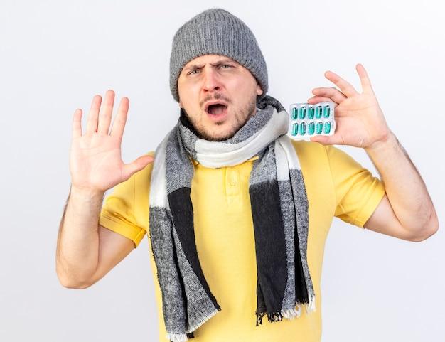 겨울 모자와 스카프를 착용하는 불쾌한 젊은 금발의 아픈 슬라브 남자는 제기 손으로 약자 및 복사 공간이 흰 벽에 고립 된 의료 약 팩을 보유하고 있습니다.
